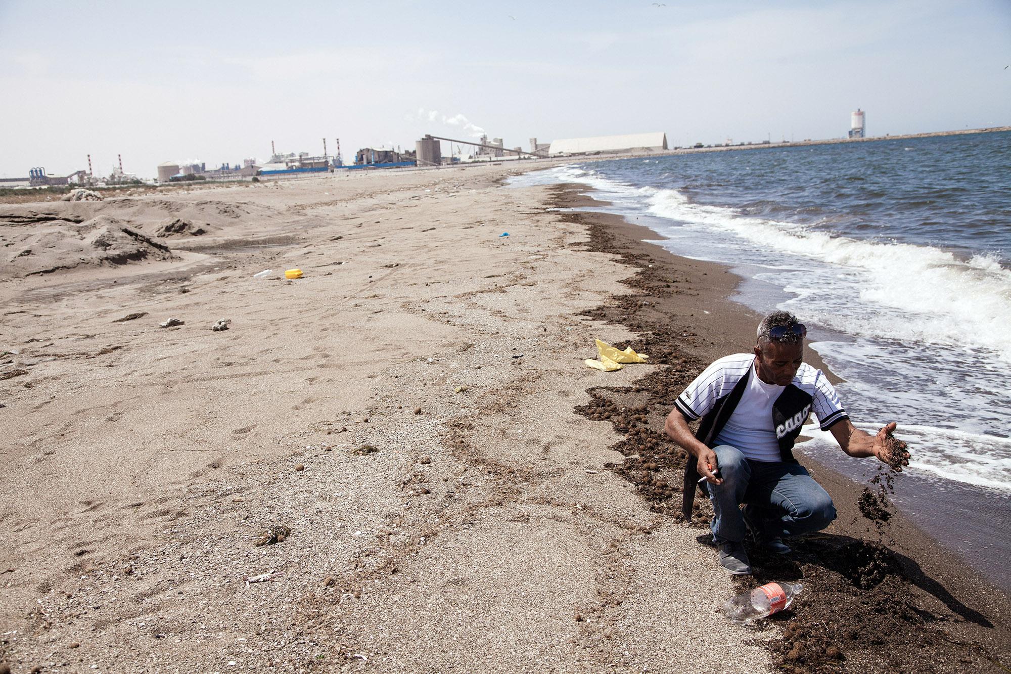 Gabes. 03 juin 2016. Meherz Hamrouni, capitaine et président du syndicat de pêche côtière de Gabes, observe le depot de phosphogypse sec issu du rejet de l'usine de traitement de photosphate. . Les déchets toxiques et polluant rejetes par l'usine du Groupe Chimique Tunisien (GCT) ont tué l'ensemble de la faune marine depuis les années 1990. Le golfe de Gabes était une zone de reproduction importante. L'usine rejette 13.000 tonnes phosphogypse sec par jour dans la Méditerranée et s'accumule sur la plage.